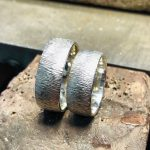 Silberne, polierte Ringe mit einer Oberfläche die fließendem Wasser ähnelt.