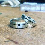 Silberne Ringe mit einer schwarzen, gravierten Linie entlang des Rückens. Die Linie wird von einem schwarzen Schmuckstein gebrochen.