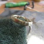 Ein goldener Ring mit einem kleinen Schmuckstein.