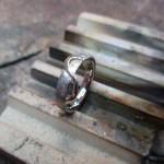 Ein silberner Ring mit gebürsteter Textur. Verziert mit einer schmalen, goldenen Welle.