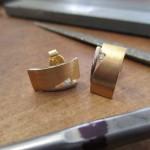 Goldene Ohrring mit einer kleinen, dreieckigen Kerbe geschlossen von einem silbernen Clip. In der Kerbe sitzt ein kleiner Schmuckstein.