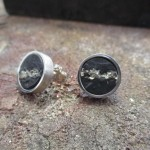 Runde Ohrringe mit silbernem Rand und einer graphitfarbenen Oberfläche, aufgebrochen durch eine Linie aus Silber.