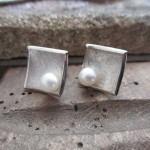 Quadratische, leicht konkave Silberohrringe. In den unteren Ecken befinden sich pro Ohrring eine Perle.