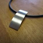 Ein rechteckiger, konvexer Silberanhänger.