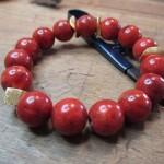 Eine Rote Perlenkette. Die einzelnen Glieder sehen aus wie reife Äpfel und werden ab und an von kleinen Goldplättchen unterbrochen.