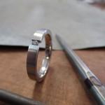 Ein schmaler silberner Ring mit einem kleinen Einschnitt in der Front. Im Einschnitt sitzt ein kleiner Schmuckstein.