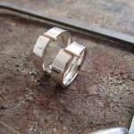 Silberne, polierte Ringe. Die Front wird durch eine schmale Linie aus Gold durchbrochen..