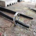 Ein schmaler, polierter silberner Ring. In der Front sitzt ein kleiner Schmuckstein, gerahmt in eine dünne Schicht Gold.