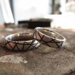 Silberne Ringe mit einer gebürsteten Textur, durchbrochen von netzähnliche, schwarzen Einkerbungen.