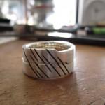 Silberne Ringe mit vertikalen, schwarzen Einkerbungen.