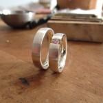 Zwei Silberne Ringe. Der Rechte ist mit einem rosafarbenen Schmuckstein versehen.