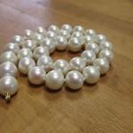 Eine weiße Perlenkette mit goldenem Verschluss.