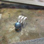 Eine kleine, blaue Kugel an einer spiralförmigen Aufhängung.
