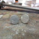 Kreisförmige, silberne Ohrringe mit jeweils einem kleinen Schmuckstein.