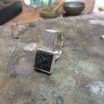 Ein silberner, quadratischer Anhänger. In der Mitte sitzt ein graphitähnlicher Stein gerahmt in Silber.
