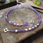 Eine violette Perlenkette. Die violetten Kettenglieder werden teils durch weiße Glieder unterbrochen.