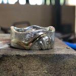 Ring, der auf einer Seite eine Wellenform aufweist. In der Front sitzt ein Schmuckstein auf einer eingravierten Muschel.