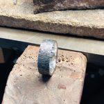 Silberner, polierter Ring mit einer Oberfläche die fließendem Wasser ähnelt.