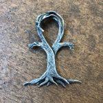 Silberanhänger aus zwei Bäumen, die ineinander greifen um die Schlafe für die Kette zu bilden.