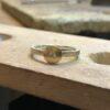 Ein silberner Ring mit runder, goldener Front in die eine kleiner Schmuckstein eingesetzt ist.