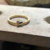 Goldener, polierter Ring mit einem silbernen Blatt an dem ein kleiner Schmuckstein hängt.