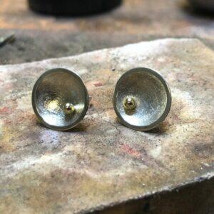 Konkave, kreisförmige Silber-Ohrstecker mit einer goldenen Kugel in der Mitte.