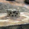 Ein silberner Ring mit alternierenden Schmucksteinen.