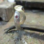 Silberner Ring mit rotem Schmuckstein, verziert durch einen goldenen, wellenförmigen Streifen.