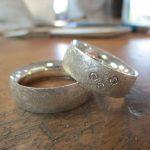 Silberne Ringe mit gebürsteter Textur und drei Schmucksteinen in der Front.