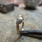 Ein goldener Ring. Die Front bildet ein silberner Halbkreis mit einem kleinen Schmuckstein.