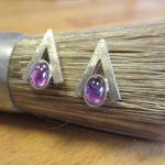 Dreieckige Ohrringe. An Stelle der Unterkante finden sich zwei ovale, violette Smucksteine.