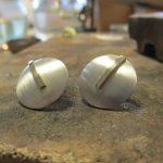 Silberne, kreisförmige Ohrstecker. Verziert mit einer goldenen Linie.